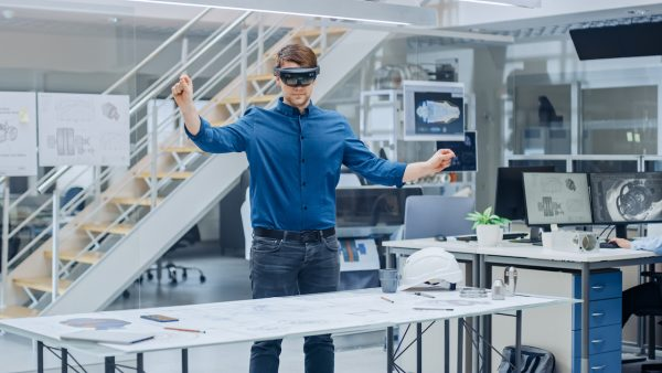Engineering Software Developer Wearing Virtual Reality Headset Uses Gestures to Interact with Augmented Reality while Designing Industrial Engine Model in Modern Facility.