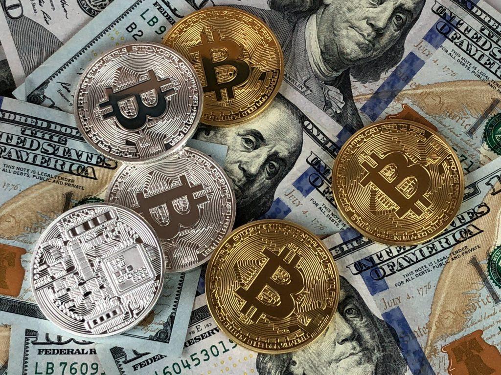 Bitcoins over over US dollar bills