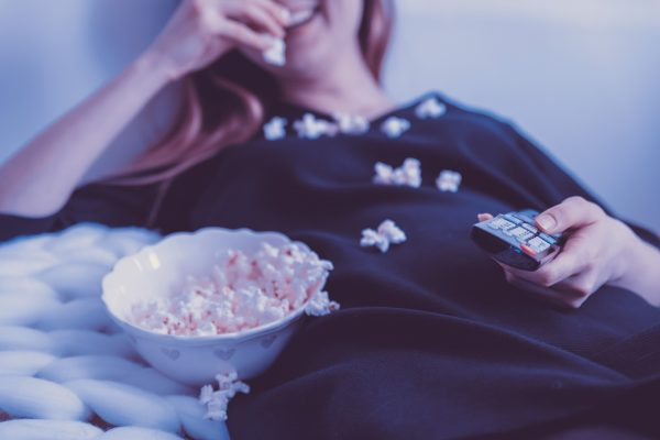 How to download movies on Hulu Lady in black dress watching television while eating popcorn.