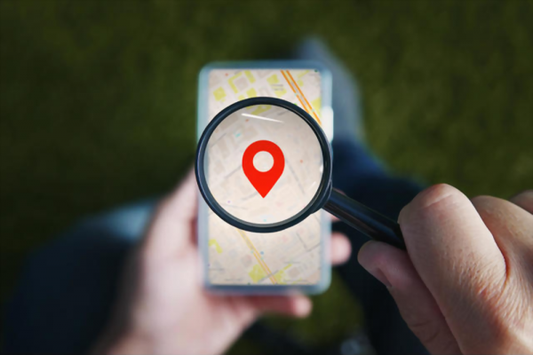 Shot of male hands holding magnifying glass with the red icon of geo-location