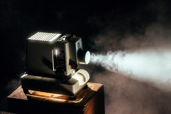 Photo of a movie projector projecting light onto something, while it's on top of a wooden table with white smoke around and a youtube free movies