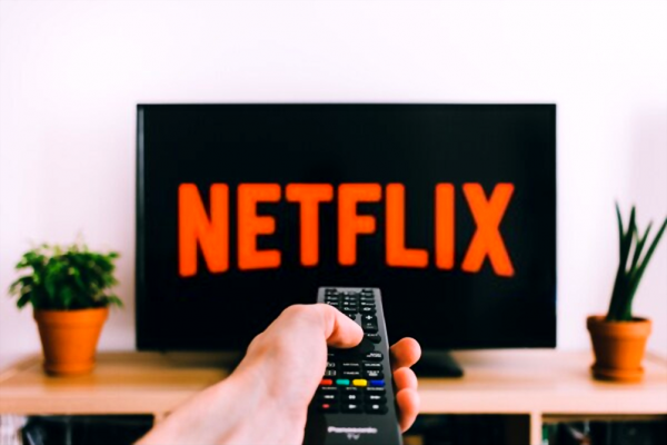 A man holding remote while watching Netflix.