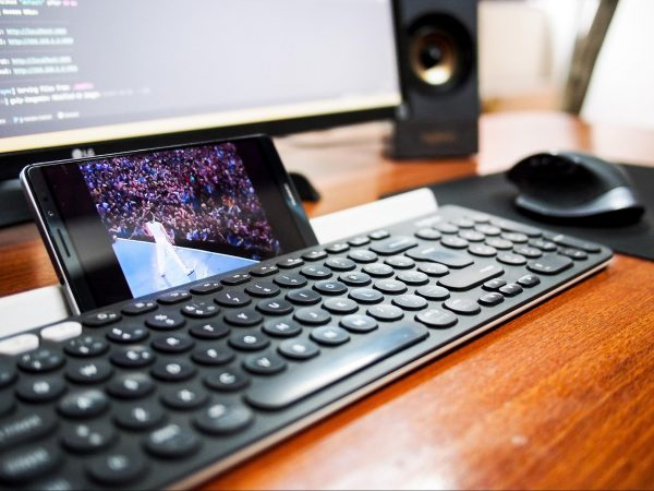 watch youtube free movies a concert in front of a crowd, the phone is upright against a keyboard with a monitor in front and a mouse to the right, all on a wooden table