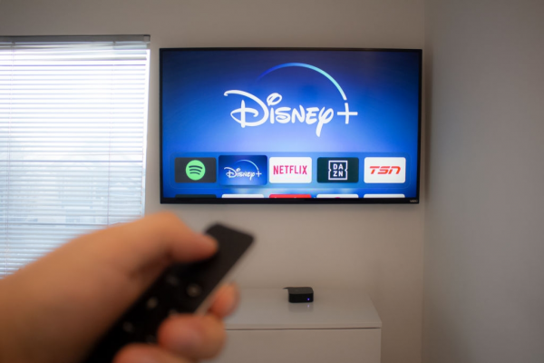 erson holds an Apple TV remote using the new Disney+ app on a Vizio TV