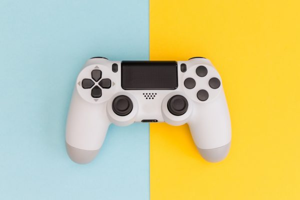 Video games white gaming controller isolated on yellow blue color background top view