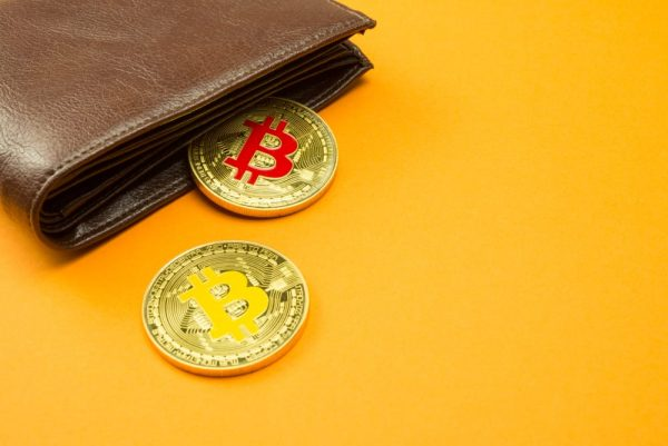 Bitcoin and Wallet on Yellow Backdrop